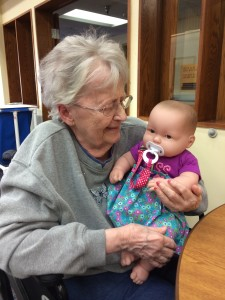 Grandma happily cuddling her Lots to Cuddle baby doll.